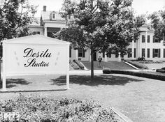 """In 1950, Lucille Ball and Desi Arnaz formed the now-famous Desilu Studios. In late 1957, they bought the RKO studios for $6 million, which seems ridiculously cheap now, especially as the purchase also included the Forty Acres studio lot in Culver City. This is where David O. Selznick filmed much of """"Gone with the Wind."""" This photo shows the Desilu sign out front of the same building where the Selznick International Pictures sign once hung."""