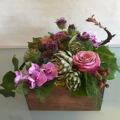 Medium custom texture box arrangement of Moody Blues roses, succulents, drumstick alliums, blackberries, clematis seed pods, tree ivy, ming fern and contorted willow in a wooden box.