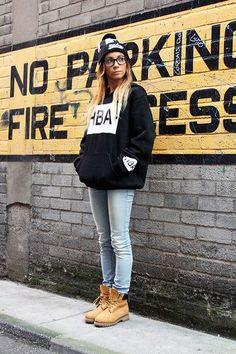 Девушка в свитшоте, облегающих джинсах и тимберлендах