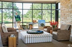 Laura and George W. Bush's Serene Texas Retreat Photos | Architectural Digest [Mr. Bush sometimes paints at an easel in the enclosed breezeway, where the windows are replaced with screens in warm weather; the ottoman and the cushions on the sea-grass chairs are covered in Sunbrella fabrics.]