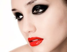 Heavy dark black eyeshadow in a glossy texture with fire engine red lips