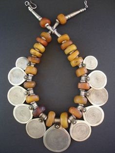 Morocco | Antique necklace with 11 Berber silver disks with niello spiral design symbolising eternity and antique fossil Amber.