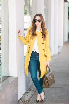rainy day outfit inspiration with a yellow trench coat and jeans