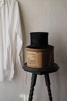 メゾン・レジェール 帽子屋の箱-antique hat box 今でも家具工房が多いパリはサン・タントワーヌ通りの住所をラベルに配して、お帽子付きと言うべきか、お箱付きと言うべきか、どちらの雰囲気も甲乙付け難く良く、往年の時そのままに。ビーバーの滑らかな毛並みが光るトップハットは美しいコンディション、ハットボックスは内側角に緩衝材が付けられており、裏表のラベルの内一方に上からグレーのペンで重ね書きした跡が御座います。セットの価格になります
