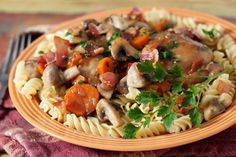 Coq au Vin. A pressure cooker twist on a classic French chicken stew made with chicken thighs, onions, carrots, mushrooms, and topped with bacon.