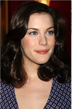 Liv Tyler. Fair skin, dark brown hair, orange tone blush and lips, classic style vneck dress.