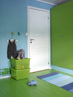 Den hvite døren skiller seg klart ut i det fargerike barnerommet. Oppbevaringskassene Vessla med hjul og lokk er fra Ikea.