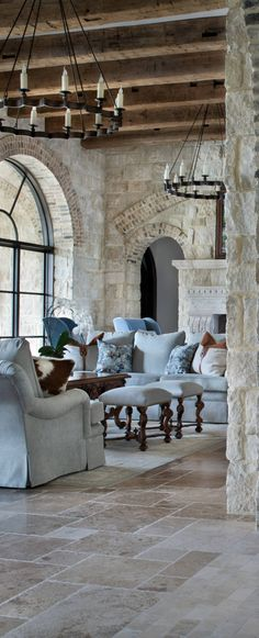 luxury rustic living room. stone walls with brick soldier rows, wood beam ceiling, London arm chairs with waterfall skirt. Turned leg ottomans. light blue upholstered furniture. DesignNashville.com lighting, designer fabrics, custom draperies and furniture