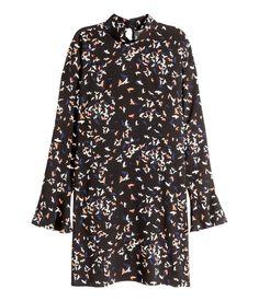 Kurzes Kleid aus Webstoff mit Musterdruck. Modell mit Stehkragen und Nackenschlitz mit Perlmuttknöpfen. Lange Ärmel mit Volant. Ungefüttert.