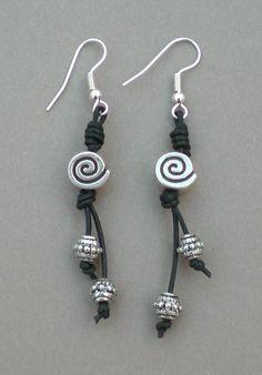 Pendientes realizados con cordón de cuero en color negro, espirales y bolitas plateadas. Gancho hippie plateado.
