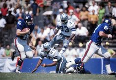 Les Shy (25) and a leaping Mike Johnson (23) in punt coverage against the New York Giants in the 1967 home opener in the Cotton Bowl. This was the very first game the Cowboys appeared with the blue outline on the helmet star.