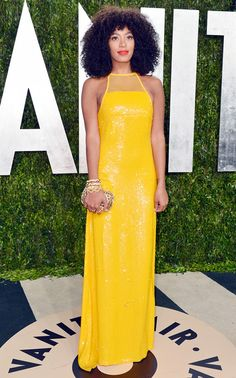 Solange wears a metallic, vivid yellow column gown by Emilio Pucci with gold accessories
