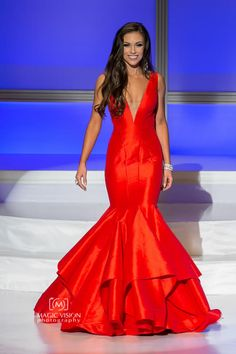 Amber Bernachi placed 1st Runner-up to Miss Universe Canada 2016 and looked stunning while doing so in this fiery red evening gown!  The Color  Red is definitely Amber's color. This bold, iridescent shade of red shines under the stage lights.  Red can sometimes be a challenging color choice depending upon the undertones of both the gown color and a contestant's skin tone. However, Amber's bronzed skin tone and dark hair color are complemented impeccably well by this shade of red.