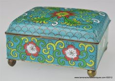 "c1920 Chinese cloisonne footed trinket/cigarette box. The box has 6 colors of enamel and depicts flowers. The enameled black CHINA mark on the base is from the early part of the 20th century. The enameling on the exterior is very nice condition with no losses. The inside is blue enameled and there is a spot on the inside of the lid that has a chip. The box measures 3 3/4"" x 3 1/4"" x 2"" in height."