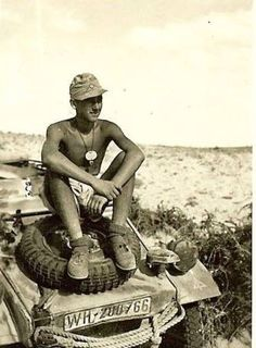 A well tanned soldier, qith the 15th Panzer Division, relaxing on his Kubelwagen in Tunisia 1943
