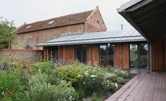 Like the contrast of wide timber cladding boards, glazed openings and zinc (?) roof
