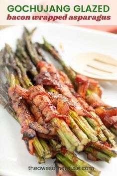 Grilled bacon wrapped asparagus glazed with Korean Gochujang sauce is the perfect summer barbecue recipe. Spicy with a touch of sweet, this easy to make, 3 ingredient recipe is delicious. | theawesomemuse.com #grilling #barbecue #asparagus #gochujang #koreanfood #baconrecipes