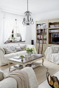 Salon - Heart home with a collection of videos and CDs.  living room, white, white interior, sofa, coffee table books, French style, beauty
