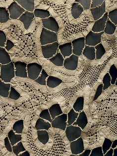 Attributed to Callot Soeurs (French, active 1895–1937). Evening Dress (detail), ca. 1920, Haute Couture. Hand– and machine–sewn black silk chiffon with hand–sewn inserts of antique ivory bobbin–made tape lace with needle–made fillings,hand–applied handmade gold metallic braided passementerie. Photo © Nicholas Alan Cope. #ManusxMachina #CostumeInstitute