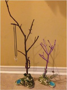 DIY Jewelry tree. Twigs were downed in an ice storm, so we chose these, baked them for 2 hrs in the oven at 200F to dry them and ensure no bugs, built a base out of air-dry clay to look like rocks and a pond, stuck the sticks in, let them dry, then glued train-model 'grass' on to make it mossy. My daughter opted to paint the one purple. I just varnished the other one. You can use a big wooden base, or an old candle holder, or a vase with rocks in it.