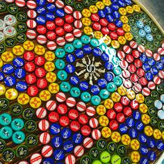 Bottle cap table.  Epoxy resin with milagros and initial.  Bottle cap art!