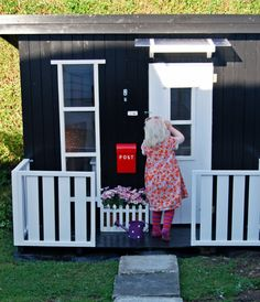 """Den gode feen: Velkommen inn i lekehuset Linda  (Norwegian for """"The Fairy Godmother: Welcome to Linda's toy house)  //  This eye-catching black & white playhouse in Norway complements the owner's full-size house which is painted white w/ a black door. It has charming details including a mailbox, flag & small flower garden  