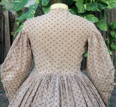 """Original Civil War Era Work Dress C 1861 two-dart construction, wide coat sleeves trimmed with narrow band of self fabric frilled at cuff & up back seams, hook & eyes at wrist, narrow stand-up collar, armholes & waist are piped, button closure (pearl with brass shank), hooks & eyes also fasten bodice, left side opening on skirt, grey wool hem tape, pocket of contrasting pocket on right side seam; bust: 38"""" waist: 29""""; front skirt length: 39"""" K Krewer collection"""