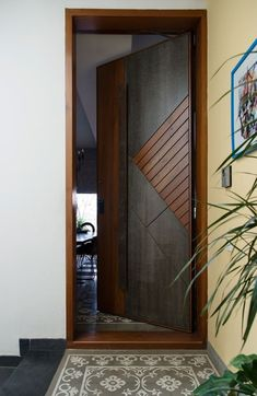 A subtle yellow wall leads to the main door of the house finished in stone and wood while the patterned tiles act as a faux rug. Photography by Prachi Damle Source by bhomesindia Modern Entrance Door, Main Entrance Door Design, Modern Wooden Doors, Door Gate Design, House Main Door Design, Modern Door, Wooden Interior Doors, Internal Doors Modern, Home Door Design