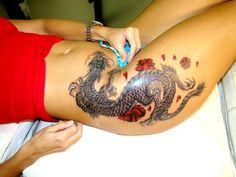 Татуировки на бедрах и животе девочки - японский дракон и сакуры