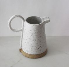 Matte white and naturally speckled hand-thrown pitcher with a unique handle. Measures approximately in diameter (at base) and H. Ceramic Pitcher, Ceramic Tableware, Glass Ceramic, Ceramic Bowls, Ceramic Clay, Slab Pottery, Ceramic Pottery, Keramik Design, Wheel Thrown Pottery