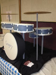 """drum set - I did this for a family reunion. there is 4 10"""" round drums, and a 8"""" seat that's all cake. the big base kick drum is faux. I just wraped the 14"""" cake pan with colored paper and then put foam board in center on both sides."""