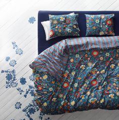 Ein Bett mit ROSENRIPS Bettwäsche-Set blau gemustert
