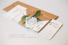 beautiful modern calligraphy invitation with green foliage, kraft belly band tied together with twine and tag. rustic elegant