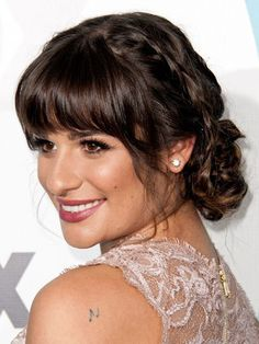 Lea Michele braided chignon with rounded bangs, flirty eyelashes and berry-colored lipstick | allure.com
