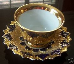 This original Meisssen teacup and saucer set is signed and numbered with gold-encrusted leaf design and a deep blue background. The teacup is 4 in diameter and the saucer is 5 3/4 in diameter. This