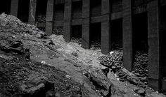 """""""As we stand at ground level I am struck how the building clearly rises from the raw rock. It looks like a lava flow has solidified in the middle of the cavernous space. I first thought the fluid-looking slope was a torrent of composting refuse left from the previous state of disrepair, but then I realise it's designed like that."""""""