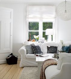 white ikea sofas, textured rug, light floors white walls