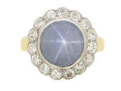 Star sapphire and diamond cluster ring. The central round cabochon star sapphire is set in an open back rub over setting with an approximate weight of 9 carats showing strong asterism, surrounded by a single row of fifteen round old cut diamonds with an approximate combined weight of 1.05 carats, grain and rub over set to open back settings. The conforming gallery has pierced work with cheniers, flowing down to raised diagonal shoulders and a D-shape shank. Yellow gold with a platinum…