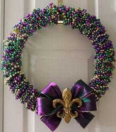 """Wreath made with leftover mardi gras beads. I included a """"D"""" made with beads in the center instead of bows."""