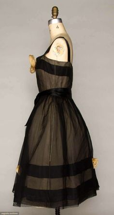 Christian Dior couture gown 1959 by designer Yves Saint Laurent. Black silk net over white silk gauze, satin shoulder straps, fitted bodice, full skirt, cloth flowers on bodice and lower skirt, built in stiffened net corset, 3 net crinolines over silk lining.