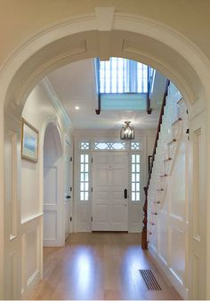 Beautiful foyer / entry hall of a new traditional home designed and built by Connor Homes in the company's Middlebury, VT factory. The foyer features paneled walls, intricate architectural details, and exquisite mouldings.