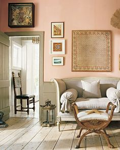 In this room, gray wainscoting and bare floors soften the vivid color of the walls, which are adorned with an asymmetrical array of small paintings, sea fans, and a framed collection of starfish. The Gustavian settee is upholstered in linen, the stool is from the mid-nineteenth century, and the side chair is baroque.