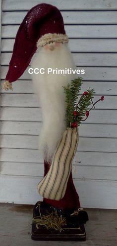 Esta Santa se encuentra en una base de madera de 4 x 4 que ha sido pintada y envejecido. Se hizo de muselina y su capa y sombrero se crea del fieltro rojo quemado. Él lleva una bolsa de tictac rellena de pino y semillas rojas. Él ha envejecido cerdos cola chenille alrededor de su sombrero y en la punta. Tiene pies de fieltro negro con campanas oxidadas. Tiene una madera de la nariz y cara dibujada a mano. Es 18 alto y 4 ancho.