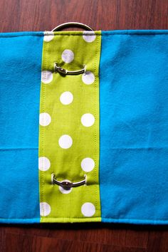 """Quiet Book Cover- """"To make the cover I took this tutorial and tweaked it a little. I basically just wrapped the fabric around a piece of Pellon and sewed it. To bind it, I used 1"""" rings and cut 6 holes in the Pellon, 2 for each ring. Then after I sewed the fabric on I used the seam ripper to cut the same hole in the inside fabric."""""""