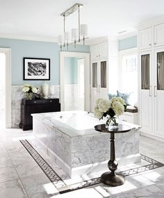 """Blue-and-White Master Bath  Abundant white cabinets and a stunning honed Calcutta marble tub surround are set off by walls painted Benjamin Moore's """"Palladian Blue."""" The black chest and contemporary chandelier are from Mitchell Gold + Bob Williams. via Traditional Home"""