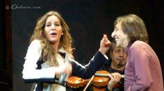 María Toledo cantando mirando hacía el público mientras hace ligeros gestos de baile mientras Antonio Carmona le observa sonriente