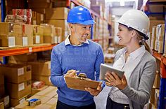 Shot of two managers looking at stock in a large warehouse - stock photo #1182113