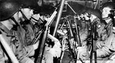 U.S. soldiers of a Glider Infantry Regiment in a glider. This picture is posed. Training ground (there is no pilot in the glider!) A medic on the right (see the Red Cross armband) wears glasses (not common in gliders!) A two right shoulder flashes are censored.