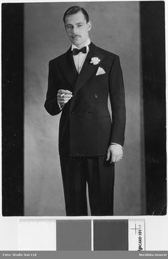 Man i mörk kostym, vit skjorta, fluga, nejlika i knapphålet samt en cigarett i handen. Nordiska Kompaniet, Fotograf: Studio Sun Ltd