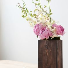 Fleur Elise. White dendrobium orchids, pink peonies and branches in a wood box. $158